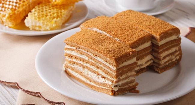 Торт Медовик со сметанным кремом нарезан на прямоугольные кусочки