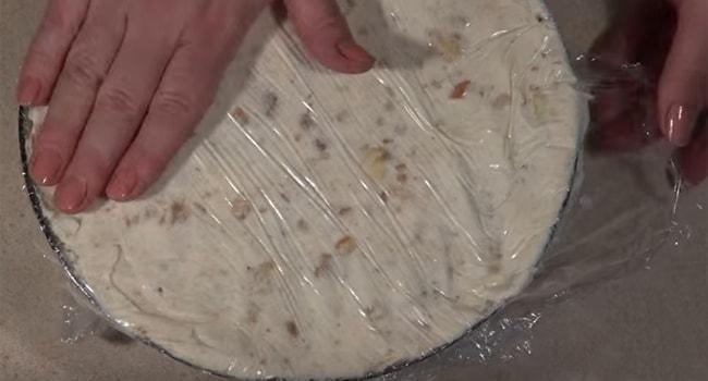 Накрываем пищевой пленкой торт и слегка утрамбовываем
