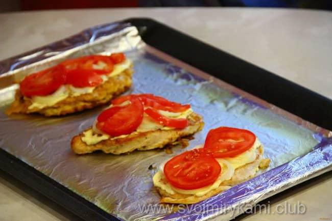 На куриные отбивные выкладываем помидоры и запекаем в духовке