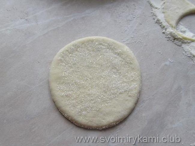 Берем в руки круглую заготовку печенье гусиные лапки, окунаем ее в сахар с одной стороны
