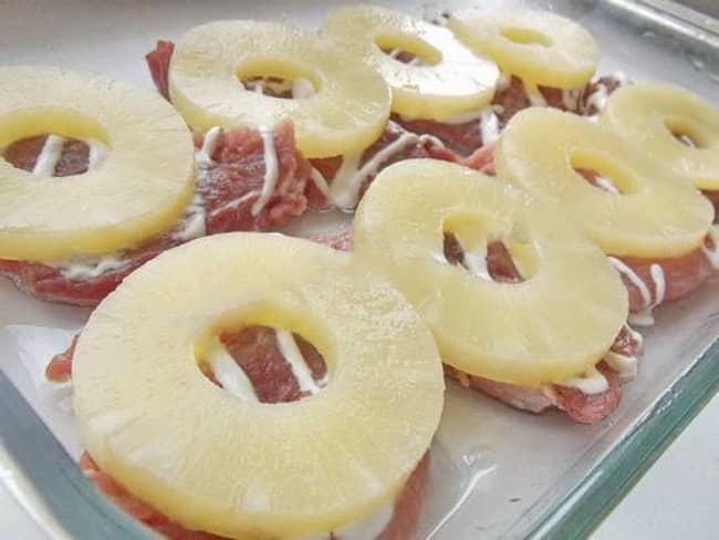 Выложите ананасы на отбитое мясо.