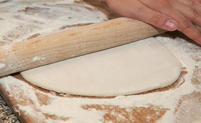 Раскатываем тесто из которого приготовим пирог с творогом и черникой.