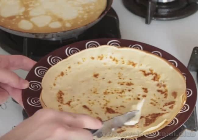 Блины, приготовленные на кислом молоке по этому рецепту, смажьте кусочком сливочного масла.