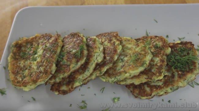 Подавайте драники из кабачков со свежей зеленью и сметаной.