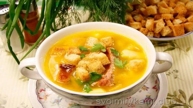 Готовый гороховый суп с копчеными ребрами подается с сухариками.