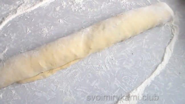 Сматывает тесто с начинкой в рулет.