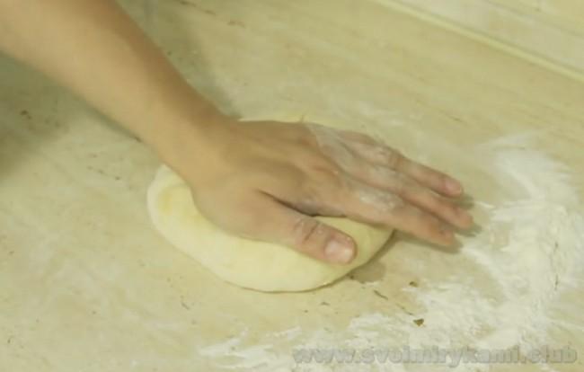 Осетинский пирог с мясом разравнивается руками в плоскую лепешку.