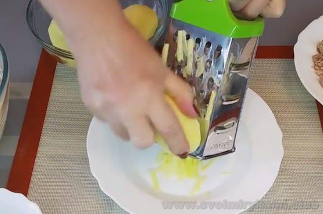 Чтобы приготовить пирог с рыбой и картофелем, натрите картофель на терке или мелко нарежьте.