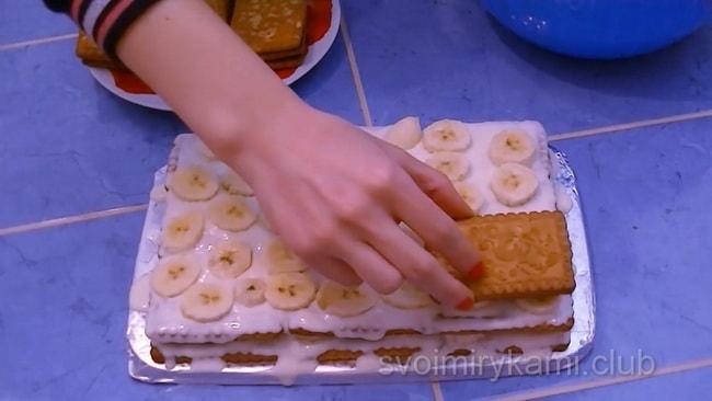 Аккуратно перемажьте слой выложенного печенья так, чтобы не повредить его, и также аккуратно разровняйте.