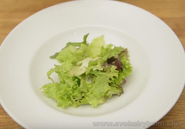 На блюдо, подготовленное для приготовления салата Нисуаз, выкладываем порванные листья салата.
