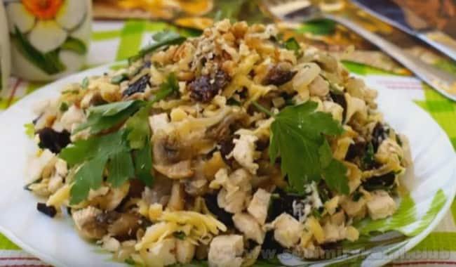 Подавая на стол салат с черносливом, курицей и шампиньонами, украсьте его зеленью.