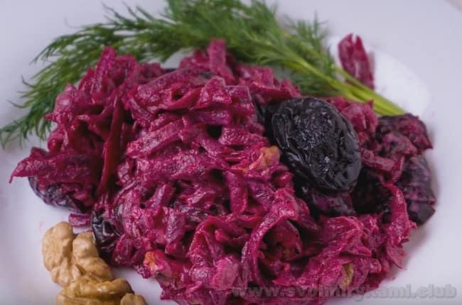 Украсьте салат с черносливом и свеклой и курицей зеленью и орешками.