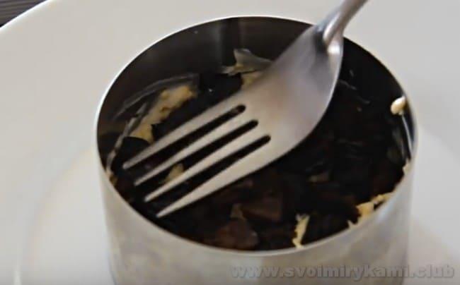 Чтобы красиво выложить салат с курицей и черносливом на блюдо, можно воспользоваться специальным кондитерским кольцом.