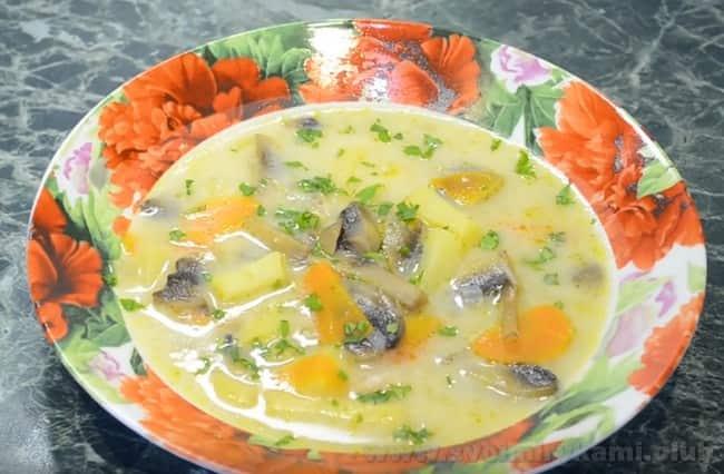Подавайте сырный суп с грибами со свежей зеленью.