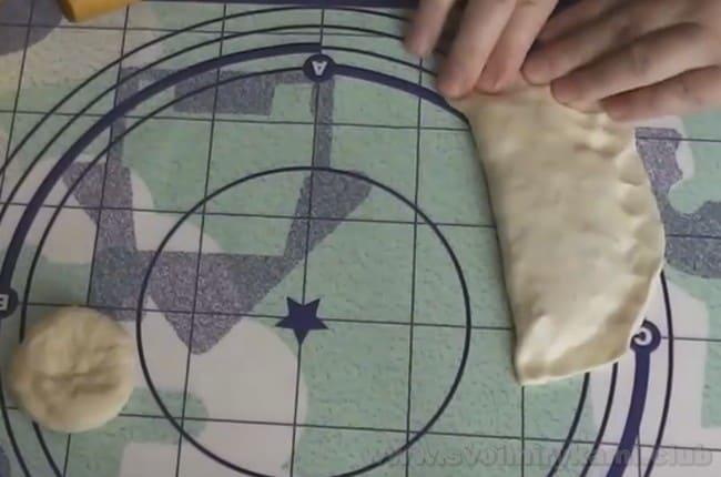 Тщательно защипните края чебурека из теста на минеральной воде.