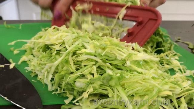 Нашинкуйте капусту ножом или с помощью овощерезки и сложите в салатник.