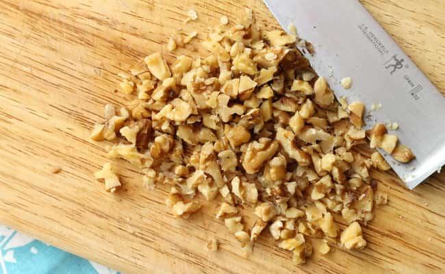Измельчаем грецкий орех ножом и добавляем в салат нежность с курицей и черносливом.