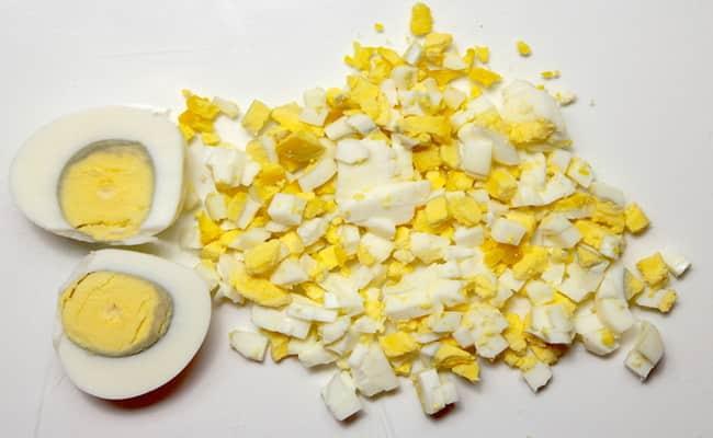 Измельчаем яйца и добавляем в салат нежность с крабовыми палочками.