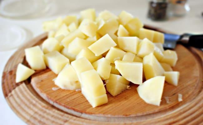 Нарезаем картофель кубиками и кидаем в суп из куриных сердечек.
