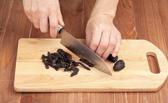 Нарезаем чернослив соломкой и добавляем в салат нежность с курицей и черносливом.
