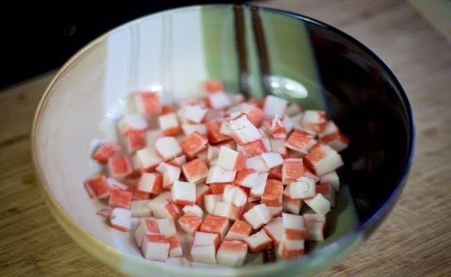 Нарезаем крабовые палочки и добавляем в салат нежность с крабовыми палочками.