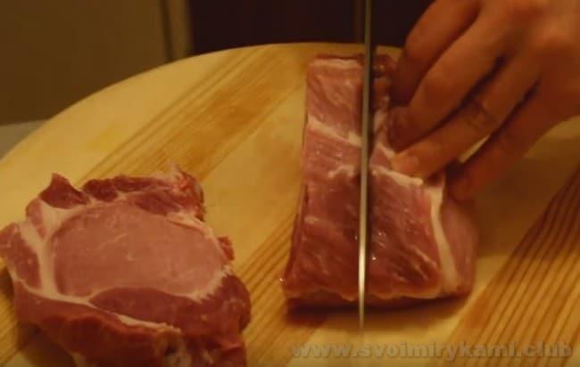 Чтобы приготовить бифштекс из свинины, надо нарезать мясо на ровные порционные куски.