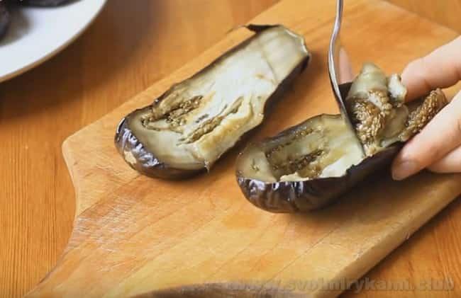 Аккуратно выньте мякоть овоща, чтобы приготовить баклажаны, фаршированные морковью и рисом по нашему рецепту.