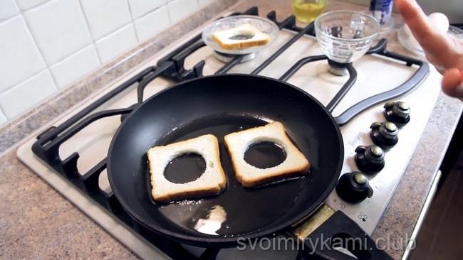 Перед тем как приготовить яичницу обжариваем ломтики хлеба.