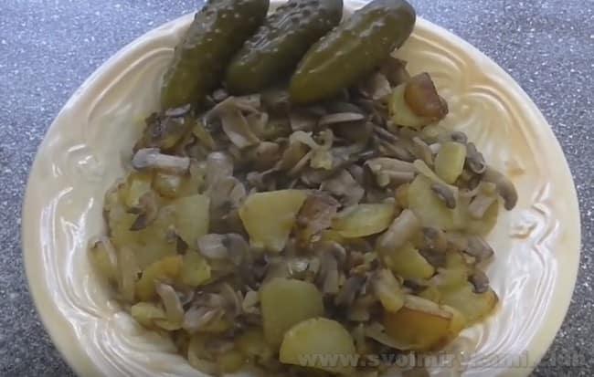 Жареная картошка с грибами на сковороде прекрасно сочетается с маринованными или квашенными огурчиками.