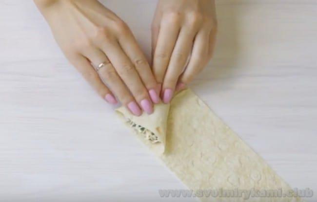 Будущий жаренный на сковороде лаваш с колбасой и сыром заворачиваем трубочками или треугольничками.