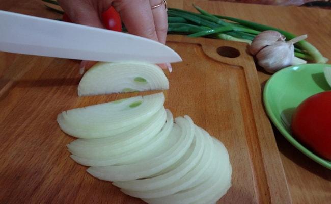 Разрезаем лук на 2 части и шинкуем полукольцами.