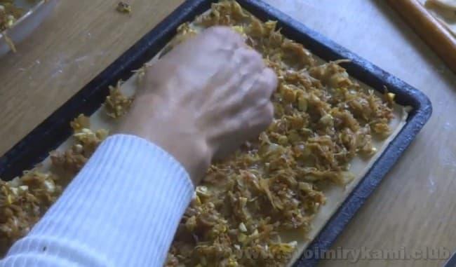 Равномерно распределите начинку по тесту для нашему будущего слоеного пирога с капустой.