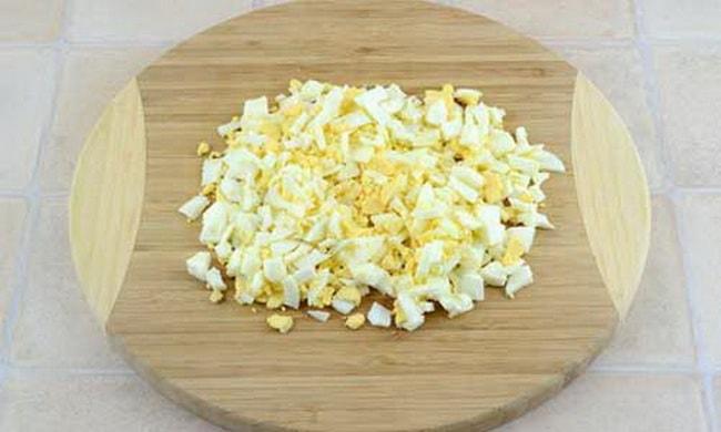 Нарежьте яйцо для приготовления пирожков со щавелем.