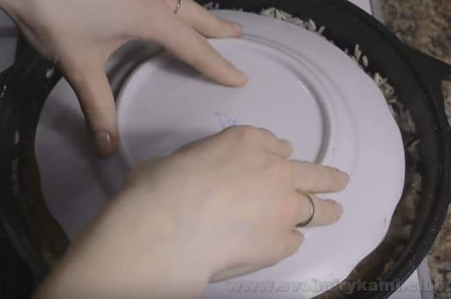 Еще один секрет удачного приготовления плова из баранины в домашних условиях - прижать блюдо тарелкой под конец готовки.