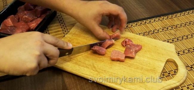 Перед тем как приготовить гуляш с подливкой нарежьте свинину.