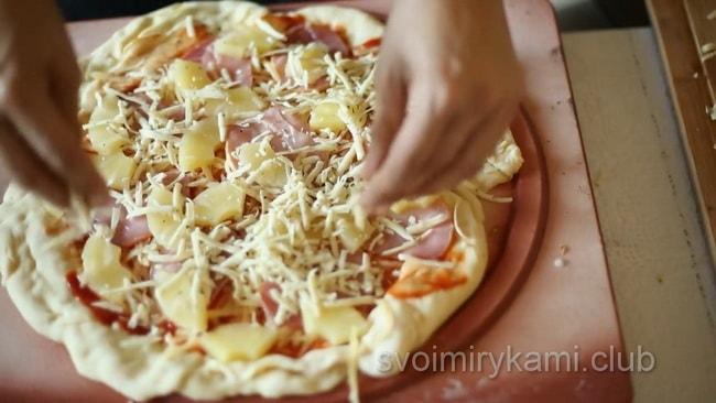 Посыпьте сыром заготовку для приготовления гавайской пиццы.