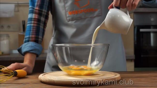 Для приготовления омлета, добавьте в яйца молоко.