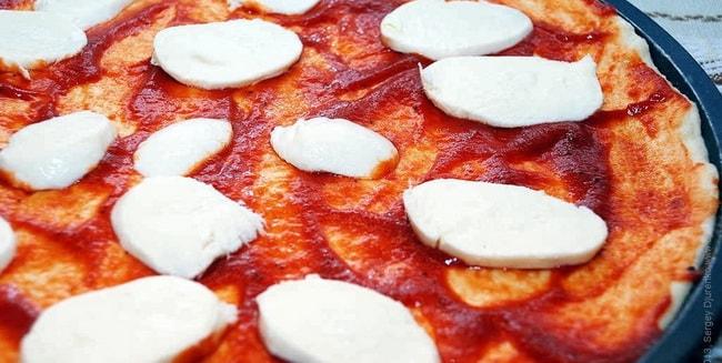 Выложите соус и мацареллу на тесто для приготовления пиццы папперони.