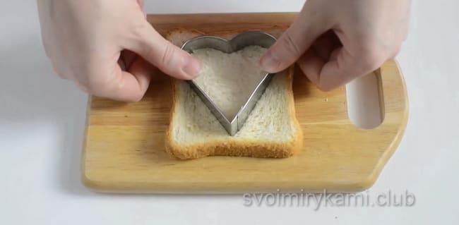 Для приготовления яичницы в хлебе с колбасой и сыром вырежьте хлеб.