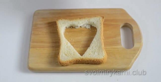 Для приготовления яичницы в хлебе с колбасой и сыром выдавите середину формочкой для печенья.