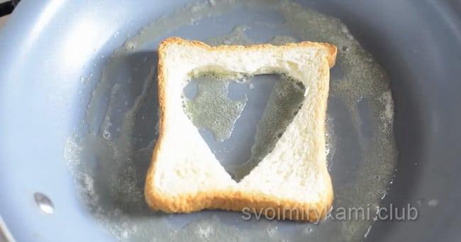 Для приготовления яичницы в хлебе с колбасой и сыром обжарьте хлеб с двух сторон.