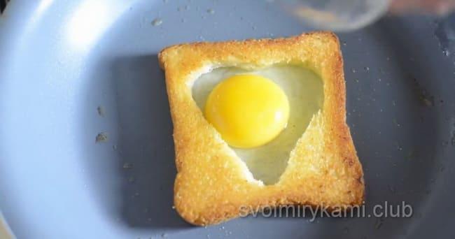 Для приготовления яичницы в хлебе с колбасой и сыром вбейте яйцо в середину.