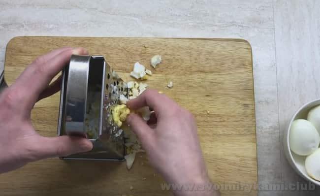 Чтобы приготовить рулет из лаваша с рыбными консервами, натрите на терке вареные яйца.