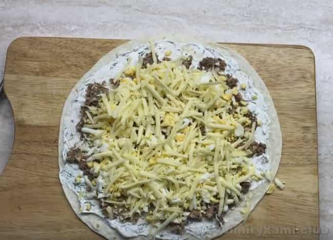 В рулет из лаваша с консервированной горбушей добавляем яйца и натертый сыр.