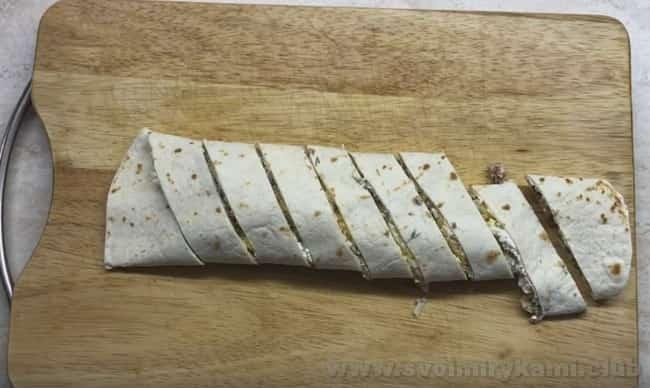 Лаваш с консервированным тунцом, скрученный в рулет, можно красиво нарезать на порционные кусочки.