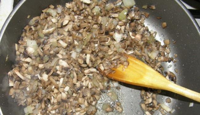 Для приготовления яичницы в хлебе с колбасой и сыром обжарьте грибы.