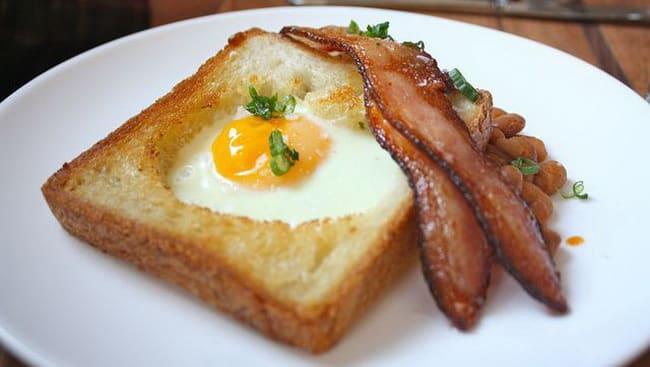 Для приготовления яичницы в хлебе с колбасой и сыром обжарьте хлеб с беконом и яйцом.