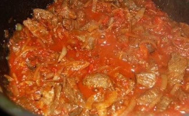 Добавляем к мясу и овощам воду, томатную пасту и специи.
