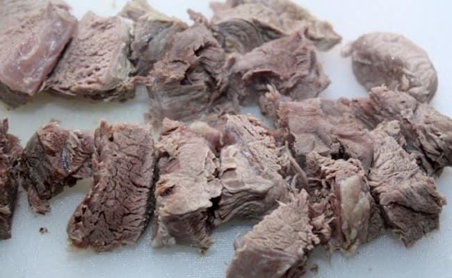 Нарезаем отварное мясо большими кусочками для гороховой каши с мясом в мультиварке.