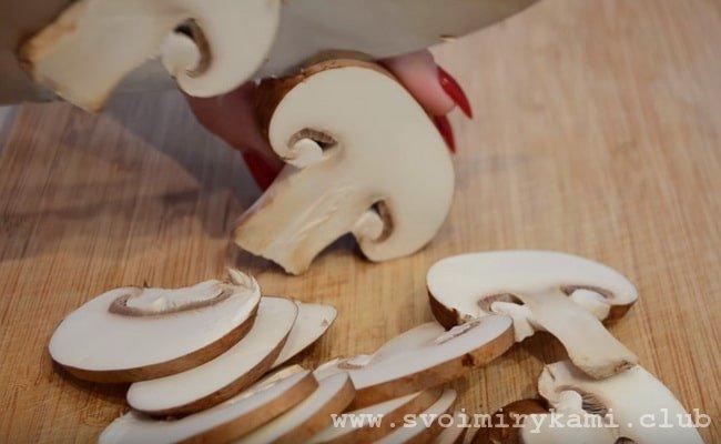 Промываем и нарезаем грибы тонкими ломтиками для грибной запеканки в духовке.